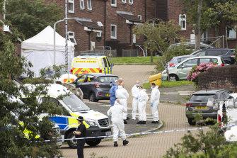 Police teams work near the shooting scene on Biddick Drive in Plymouth.