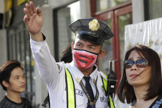 A security guard wearing a protective mask assists a woman in Manila. Philippine President Rodrigo Duterte authorised sweeping quarantines to fight the coronavirus.