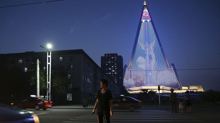 "A North Korean woman crosses a road as a light show is projected on the pyramid-shaped Ryugyong Hotel in Pyongyang to commemorate last week's 65th anniversary of the end of the Korean War, which the country celebrates as the day of ""victory in the fatherland liberation war""."