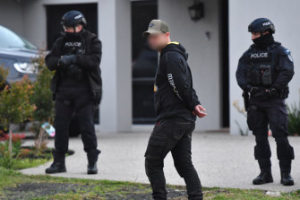 A man paces outside the Keilor Lodge home as police raid the property.