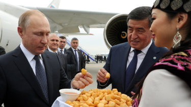 Russian President Vladimir Putin, left, and Kyrgyzstan's President Sooronbai Jeenbekov, second from right, sample a Kyrgyz traditional meal during their meeting in Bishkek, Kyrgyzstan, in March.