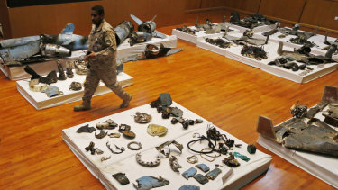 A Saudi military officer walks by what was described as the remains of Iranian cruise missiles and drones used in an attack that targeted the heart of Saudi Arabia's oil industry.