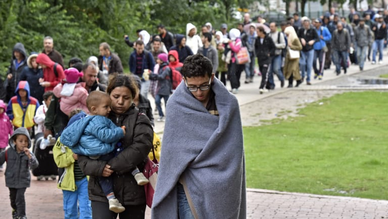 Migrants walk from the main station in Dortmund, Germany, to a reception centre at the height of the migrant crisis in 2015.