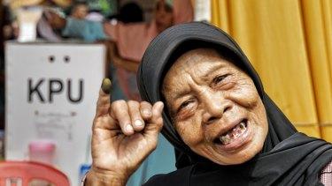 Umi, a rubbish picker from a rural slum in Kali Baru village, North Jakarta, shows her inked finger after casting her vote.