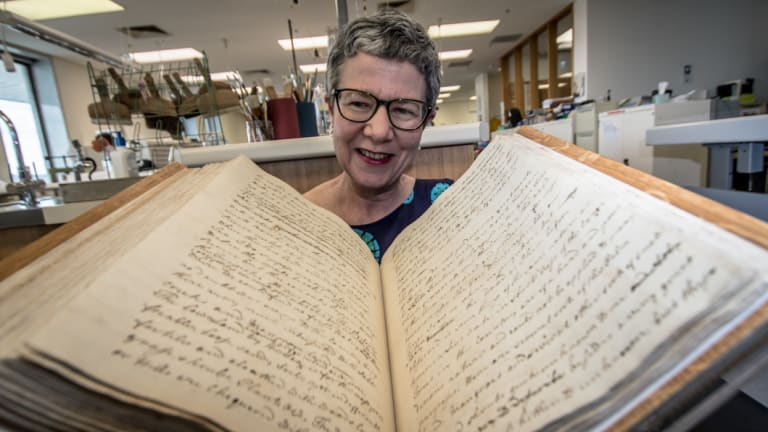 Pictured with the 250 year old captain's log from the Endeavour sailing, National Library of Australia director general Dr Marie-Louise Ayres announce the upcoming major international exhibition, Cook and the Pacific.