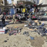 People and security forces gather at the site of a deadly bomb attack in a market selling used clothes in Iraq.