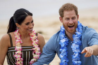 """FILE - In this Friday, Oct. 19, 2018 file photo Britain's Prince Harry and Meghan, Duchess of Sussex meet with a local surfing community group, known as OneWave, raising awareness for mental health and wellbeing in a fun and engaging way at Bondi Beach in Sydney, Australia. In a stunning declaration, Britain's Prince Harry and his wife, Meghan, said they are planning """"to step back"""" as senior members of the royal family and """"work to become financially independent."""" A statement issued by the couple Wednesday, Jan. 8, 2020 also said they intend to """"balance"""" their time between the U.K. and North America. (Dominic Lipinski/Pool via AP)"""