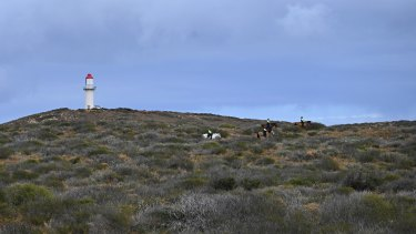 Mounted police scour the hills behind the Blowholes campsite, where Cleo Smith went missing from, on Thursday while soldiers fly a drone from near a lighthouse.