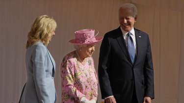 US President Joe Biden and first lady Jill Biden smile while standing with Britain's Queen Elizabeth II watching a Guard of Honour march past before their meeting at Windsor Castle.