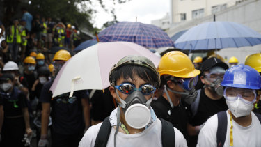 Protesters wearing gas masks and helmets stand near the police headquarters during a demonstration in Hong Kong, China, on Friday.