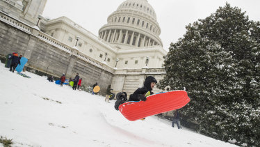 Two children go over a ramp as they sled on Capitol Hill, Washington.