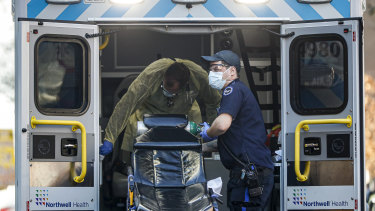 Medical workers load oxygen and disinfect surfaces of an ambulance outside a COVID-19 testing side at Elmhurst Hospital Centre.
