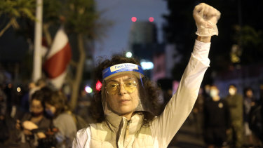 A protester wearing a protective face shield at an anti-government demonstration outside the headquarters of the Lebanese central bank in Beirut, Lebanon.