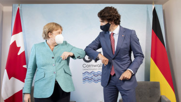Elbow bumps not conferring gravitas:  Canadian Prime Minister Justin Trudeau welcomes German Chancellor Angela Merkel at the start of a bilateral meeting at the G7 Summit in Cornwall.