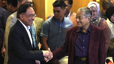 Malaysian Prime Minister Mahathir Mohamad shakes hand with his then-designated successor Anwar Ibrahim at the weekend.
