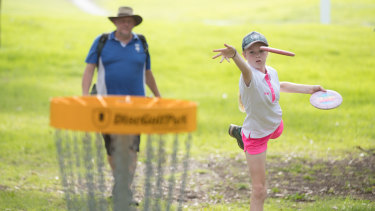 Melbourne Disc Golf Club president Jeff Brunsting and junior competitor Evelyn Heath get their eye in.