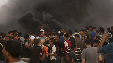 Protesters gather while burning tyres near the fence of the Gaza Strip's border with Israel on Friday.