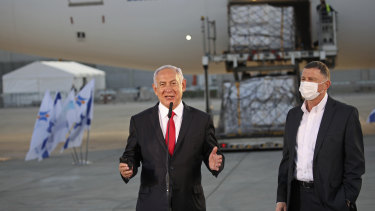 Israeli PM Benjamin Netanyahu, centre, and Health Minister Yuli Edelstein, with a shipment of Pfizer coronavirus vaccine, at Ben Gurion Airport near the city of Lod, on Sunday.