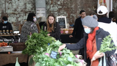 About half of shoppers and stallholders wore face masks at Carriageworks Farmers Markets, which reopened Saturday.