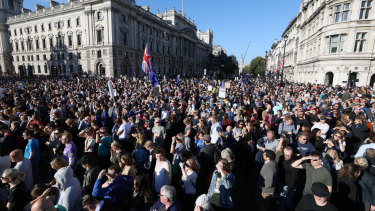 A Union flag, also known as a Union Jack, stands above crowds of demonstrators as they listen to speeches on Parliament Square following the anti-Brexit People's Vote march in London, UK.