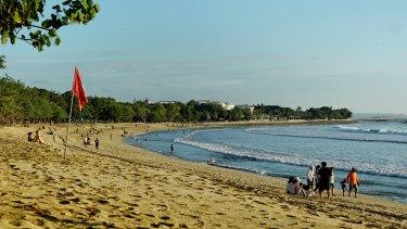 Visitors return to the beach at Kuta.