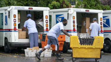 Letter carriers load mail trucks for deliveries at a US Postal Service facility in McLean, Virginia.
