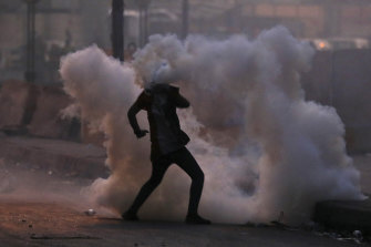 An anti-government protester finds himself in a cloud of tear gas during a demonstration in Baghdad.