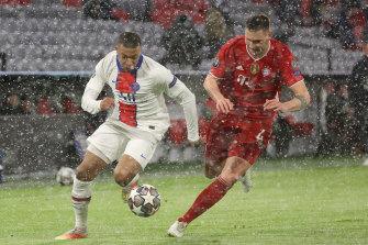 Kylian Mbappe (left) gets away from Bayern Munich's Niklas Suele.