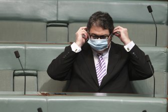 Nationals MP George Christensen removes his mask in order to share his view about how masks don't work.