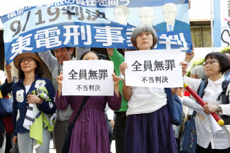 """A group of demonstrators with banners reading """"unjust sentence"""" stand in front of Tokyo District Court on Thursday."""