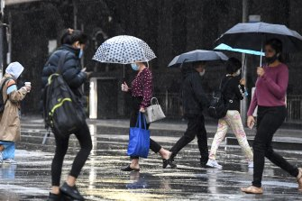 Commuters try to avoid the rain in Melbourne on Friday.