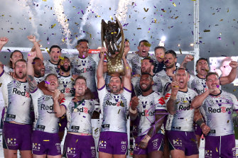 The Storm celebrate with the premiership trophy at ANZ Stadium.