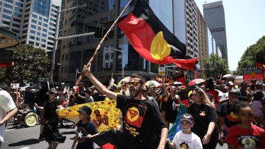 Taking to the streets:  Invasion Day Rally in Sydney on Saturday. David Dungay 's nephew Paul Dungay waves the Aboriginal flag.
