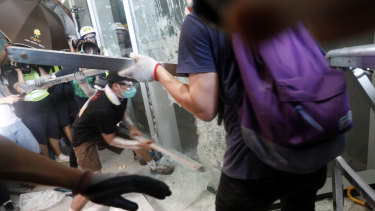 Demonstrators use metal bars to break a window at the Legislative Council building.
