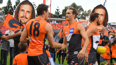 Giant step: Jeremy Cameron (left) congratulates 150th gamer Phil Davis before the game.