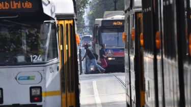 Pedestrians cross in front of trams on Swanston Street last year.