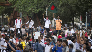 A Bangladeshi student waves the national flag and shouts slogans as they block a road during a protest in Dhaka.