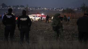 Rescue crews examine the scene of the helicopter crash near Puebla City.