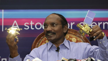 Indian Space Research Organisation chairman Kailasavadivoo Sivan displays a model of Chandrayaan 2 orbiter and rover during a press conference in Bangalore.