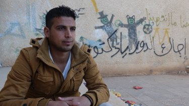 """Mouawiya Syasneh, now 20, poses for a photo near his old school and a graffiti reads """"Doctor, your turn"""", in Daara, Syria."""