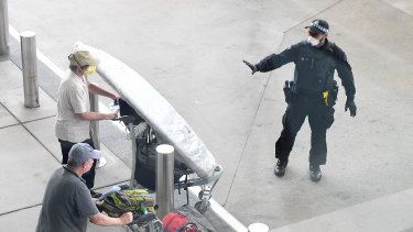 A police officer instructs a returning passenger to stop after arriving on a flight in Brisbane Airport on Thursday.