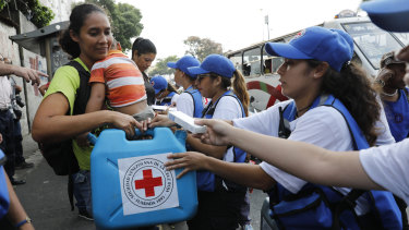 A woman with a child receives an empty container for water and water purification pills during the Red Cross' first aid shipment in Caracas, Venezuela, on Tuesday.