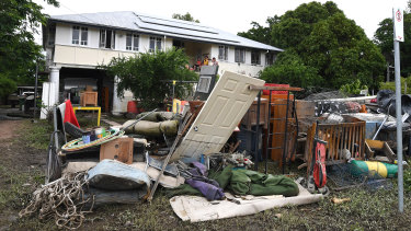 A large pile of water-damaged items in front of a flooded house in the Townsville suburb of Hermit Park on Wednesday.