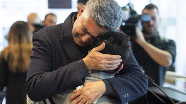 Ryan Pourjam, 13, son of Mansour Pourjam, is embraced by family friend Mahmoud Rastgou, after a ceremony at Carleton University in Ottawa.