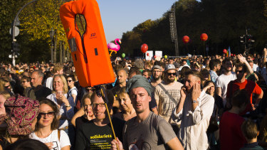 A man holds up a life jacket as he attends with thousands of protesters a demonstration with the slogan 'indivisible' and for solidarity instead of exclusion in Berlin, Germany on Saturday.