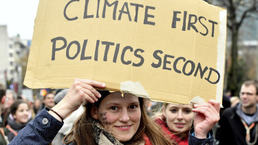 A demonstrator holds a placard which reads 'climate first, politics second' during a 'Claim the Climate' march in Brussels, on Sunday.