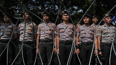 Members of the Indonesian National Police stand guard outside the General Elections Commission in Jakarta.