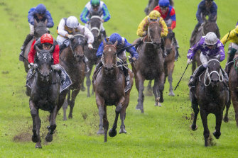Con Te Partiro, left, skips through the mud in the Coolmore Classic.