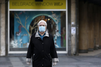 An elderly woman wearing a mask against the spread of the new coronavirus walks during a curfew in downtown Belgrade, Serbia.