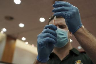 A healthcare worker fills a syringe with the AstraZeneca vaccine.
